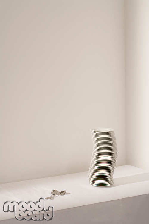 Spoons next to stack of plates on table
