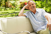 Man Relaxing in back yard on sofa portrait