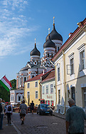 Tallinn, Estonia -- July 23, 2019. Tourists explore a side street in Tallin, Estonia, with Alexander Nevsky Cathedral looming in the background.