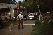 "BESSEMER, AL – OCTOBER 8, 2011: Blues legend Henry ""Gip"" Gipson, 90, strums an acoustic guitar in front of his home before a performance in his backyard juke joint.<br /> <br /> After an altercation with the KKK in the 60's rendered his left hand badly broken, Gipson's method of guitar playing had to change. ""I had to crowd the strings,"" Gipson said, describing the method that he adopted. Today, Gipson operates Gip's Place, one of few true remaining juke joints in the country. ""Music don't care no color,"" Gipson said. ""And that's why I love blues, because blues deals with a story to tell you."""