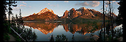 Panoramic image of the full moon setting over the Teton Range along Jenny Lake in Grand Teton National Park.