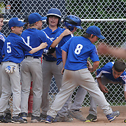 A young batter is congratulated by team mates after hitting a home run during the Norwalk Little League baseball competition at Broad River Fields,  Norwalk, Connecticut. USA. Photo Tim Clayton