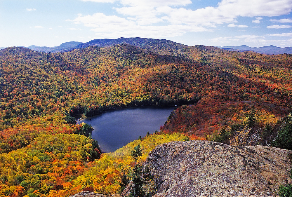 Siamese Wilderness, Adirondacks, NY.<br /> From the cliffs of Peaked Mountain you look down on this little jewel, looking like a dark sapphire in the dazzling color.  Rows of cumulous stretched to rows of minor peaks on the horizon-to have to leave was disappointing.