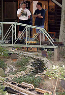 Jack Wilson (left) talks to a visitor as a g-scale train crosses a bridge over a pond in his back yard..  It's part of Jack and Sharon Wilson's 'Little River Railroad' during the open garden tour for garden railroad clubs from Cincinnati, Columbus and Indianapolis, Sunday, July 15, 2007.