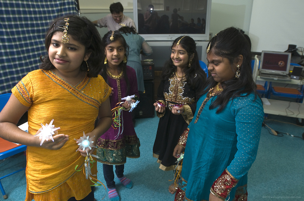 Dance students Arika Diwedi, 10, left, Shloka Nair, 9, Preeti Tanwani, 8, center, and Kavya Nair, 10, prepare to perform Nachale: The Bollywood Dance Workout, during the English Conversation Club: Dance and Dialogue event Saturday April 9, 2011 at the Iroquois Branch of the Louisville Free Public Library in Louisville, Ky. Henna and Bindi followed the Bollywood dance lesson, and then volunteers were paired with English language learners to work on conversation skills. (Photo by Brian Bohannon)