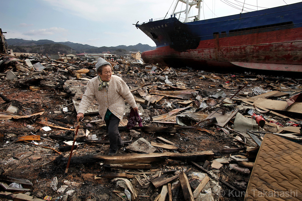 A woman looks for her belongings on debris scatter around Shinhamacyo area in Kesennuma, Miyagi, Japan on March 29, 2011 after massive earthquake and tsunami hit northern Japan. More than 20,000 were killed by the disaster on March 11.<br /> Photo by Kuni Takahashi