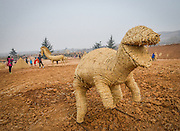 LUOYANG, CHINA - MARCH 16: (CHINA OUT) <br /> <br />  straw dinosaur is seen at a construction site on March 16, 2016 in Luoyang, Henan Province of China. Various straw dolls like dinosaurs, ducks, Minions, elephants, pandas and small trains as well we others are made at a construction site which attracted citizens and visitors. <br /> ©Exclusivepix Media
