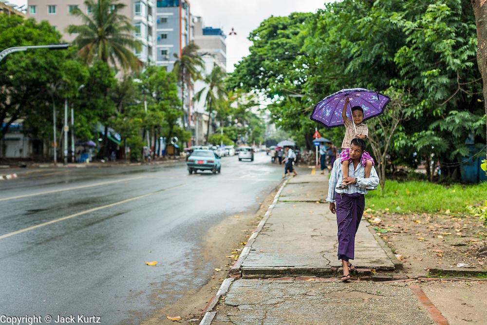 12 JUNE 2013 - YANGON, MYANMAR:  A man carries his son through a rain storm in Yangon, Myanmar.        PHOTO BY JACK KURTZ