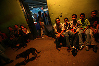 People sit out front of a store at nighttime in Leiva, a small remote village in the southern Colombian state of Nariño, on June 24, 2007. Leiva has long been a coca village; most of the people who live in the area have relied on the coca business in order to make ends meet. But with increasing pressure by the Colombian government, with fumigation and manual eradication of the coca fields, many people are now trying to figure out what the will do if they can?t rely on their meager coca profits. (Photo/Scott Dalton)