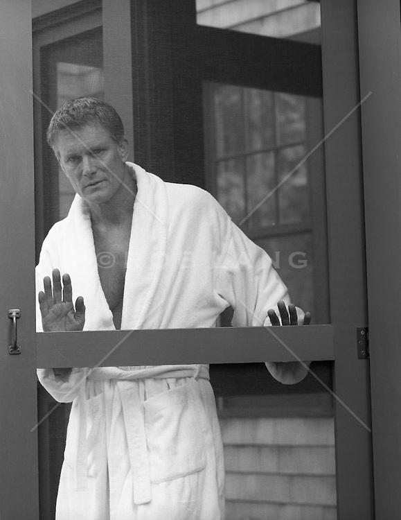 handsome man in a bathrobe opening a screen door