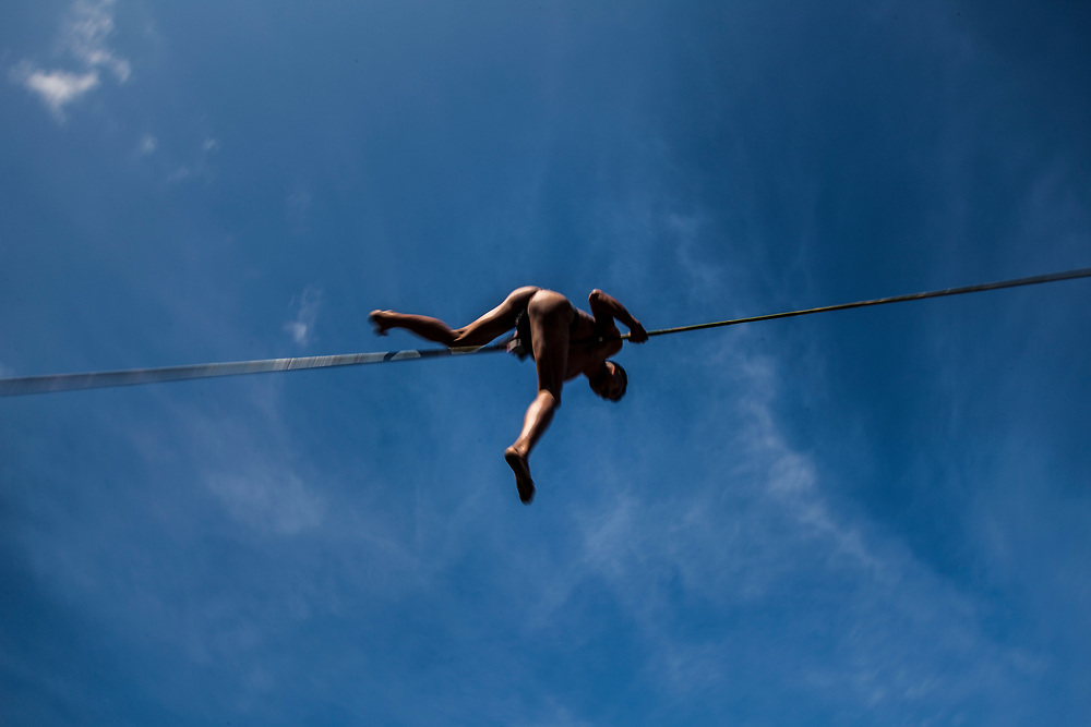 A tribesman at the Hornbill Festival in Nagaland climbs across and bounces upon a taut bamboo rope.