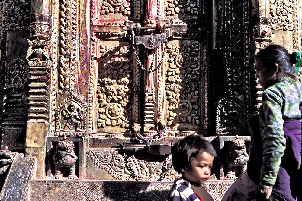 Changu Narayan temple precinct; a World Heritage site, Kathmandu valley.  Closeup of locked temple door; woman and child passersby..