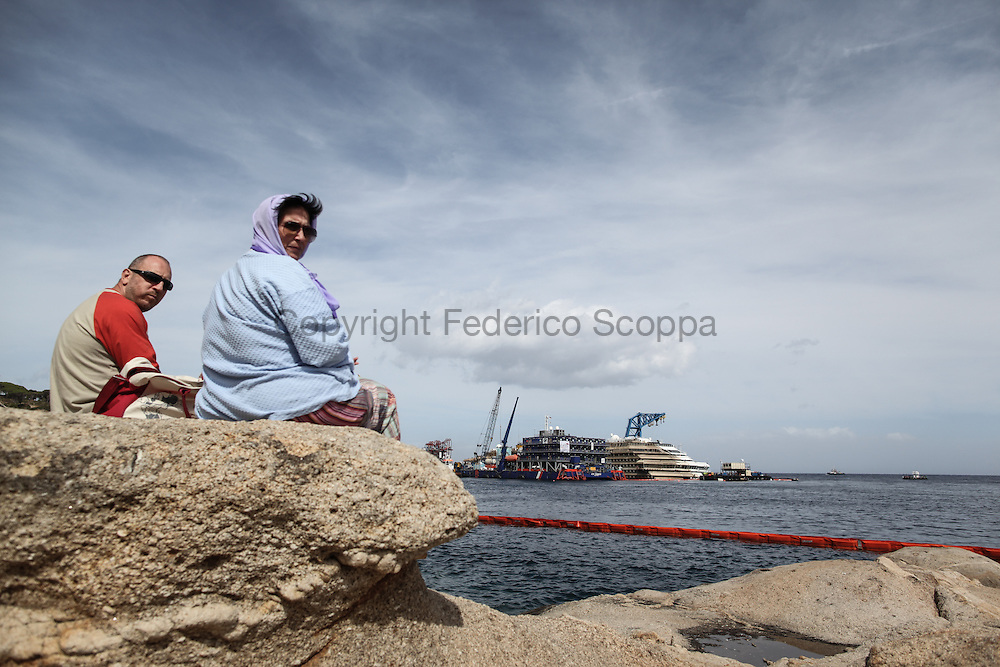 Tourist looking at the Costa Concordia wreck yard the day after the end of the parbuckling operations