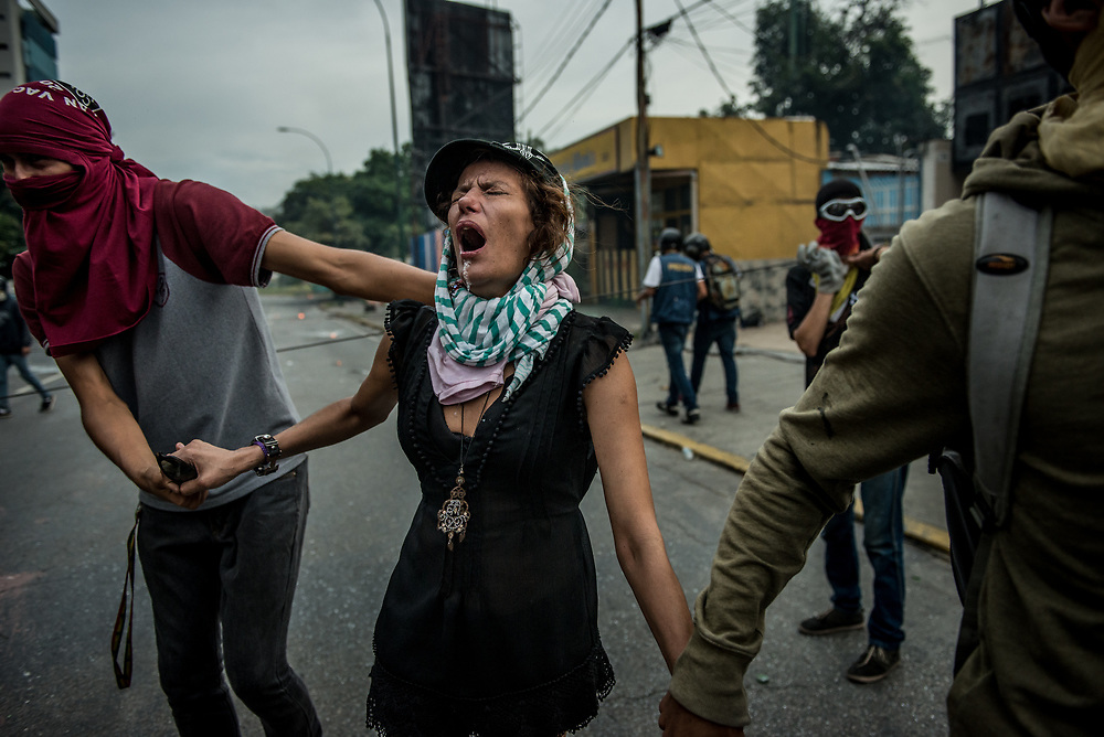 CARACAS, VENEZUELA - MAY 22, 2017: Anti-government protesters assist a woman having difficulty breathing after being tear gassed by National Guard soldiers during clashes in Caracas. The streets of Caracas and other cities across Venezuela have been filled with tens of thousands of demonstrators for nearly 100 days of massive protests, held since April 1st. Protesters are enraged at the government for becoming an increasingly repressive, authoritarian regime that has delayed elections, used armed government loyalist to threaten dissidents, called for the Constitution to be re-written to favor them, jailed and tortured protesters and members of the political opposition, and whose corruption and failed economic policy has caused the current economic crisis that has led to widespread food and medicine shortages across the country.  Independent local media report nearly 100 people have been killed during protests and protest-related riots and looting.  The government currently only officially reports 75 deaths.  Over 2,000 people have been injured, and over 3,000 protesters have been detained by authorities.  PHOTO: Meridith Kohut for The New York Times