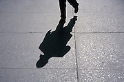 Shadow of white collar worker walking on the pavement
