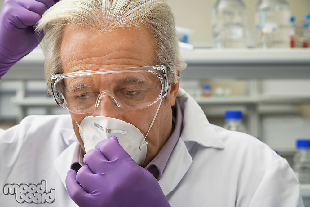 Scientist putting on safety mask in laboratory