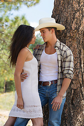 young cowboy holding a girl outdoors