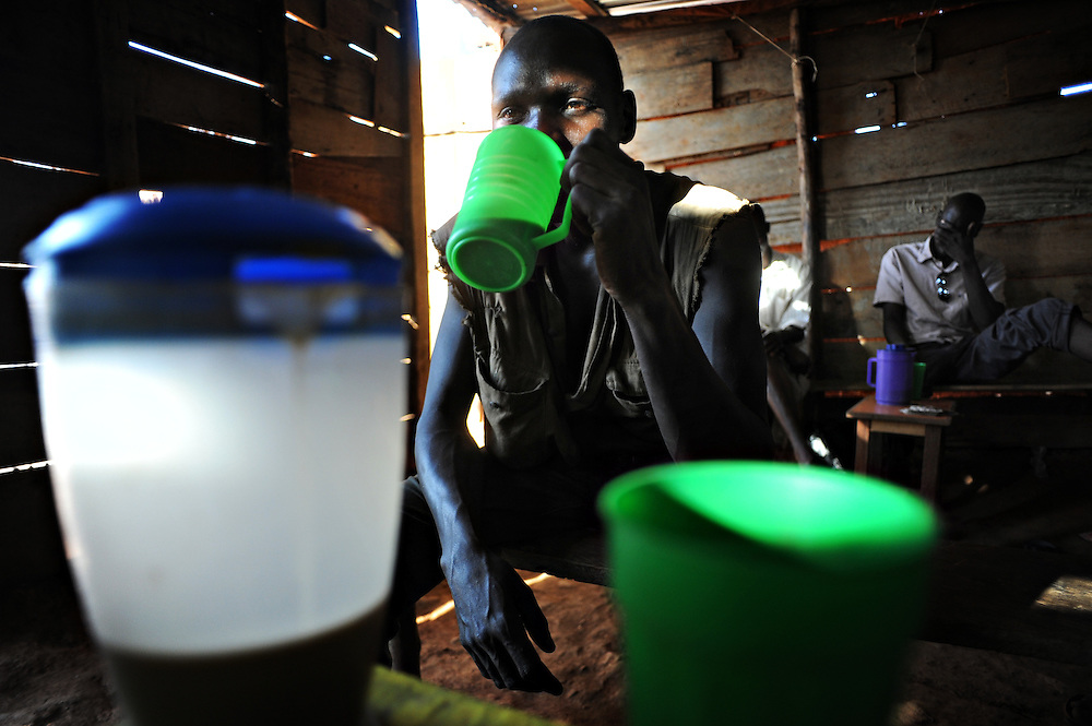 "12-03-22   -- KAMPALA, UGANDA --   James Omejja, from Dokolo in northern Uganda, drinks kwete, a millet based local brew, at a bar in the Acholi Quarter on March 22. Omejja says he, like many others, drinks to forget the past. ""In 2003, our school was invaded so we had to take off, but 12 students were killed by that time.  You have to rescue your life."" In the Acholi Quarter, life is also difficult he says. "" It is tremendously difficult. We can't get good jobs to support ourselves. Here they say we northerners are bad people, so we segregate ourselves. So long as your name begins with 'o' , it is cursed."" Photo by Daniel Hayduk"