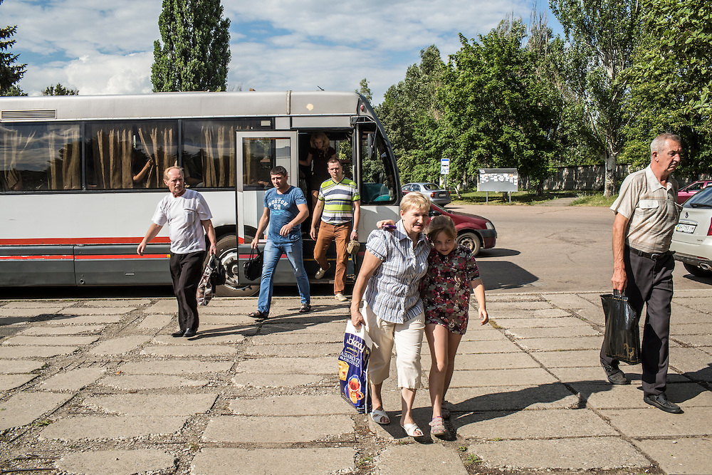 SVITLODARSK, UKRAINE - JULY 8, 2016: Passengers get off a bus in Svitlodarsk, Ukraine. The village is located less than ten miles from the front lines with rebel-controlled territory. CREDIT: Brendan Hoffman for The New York Times