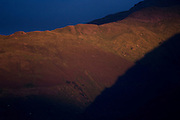 Late orange sunlight plays across upper slopes of Sgorr Dhearg, a mountain in Glencoe, Scotland.