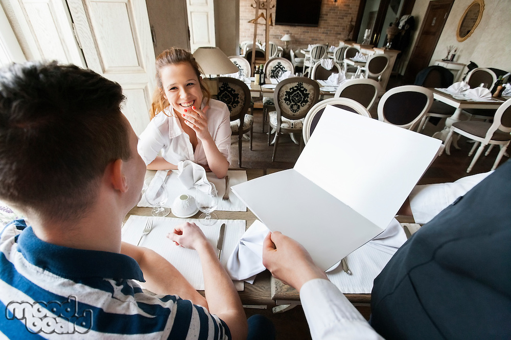 Cropped image of waiter showing menu to couple in restaurant
