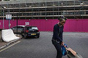 London, England, UK, May 31 2018- A resident passing in front of a building being demolished at Aylesbury Estate,  a housing estate in Walworth, South East London. <br /> Aylesbury  estate, once the largest estate in Europe, is currently undergoing a major regeneration programme by demolishing and replacing of the dwellings with modern houses controlled by a housing association. Some residents and activists still protest against the demolition and the gentrification of London.<br /> London is facing a major housing crisis, due to rising cost and under-supply.