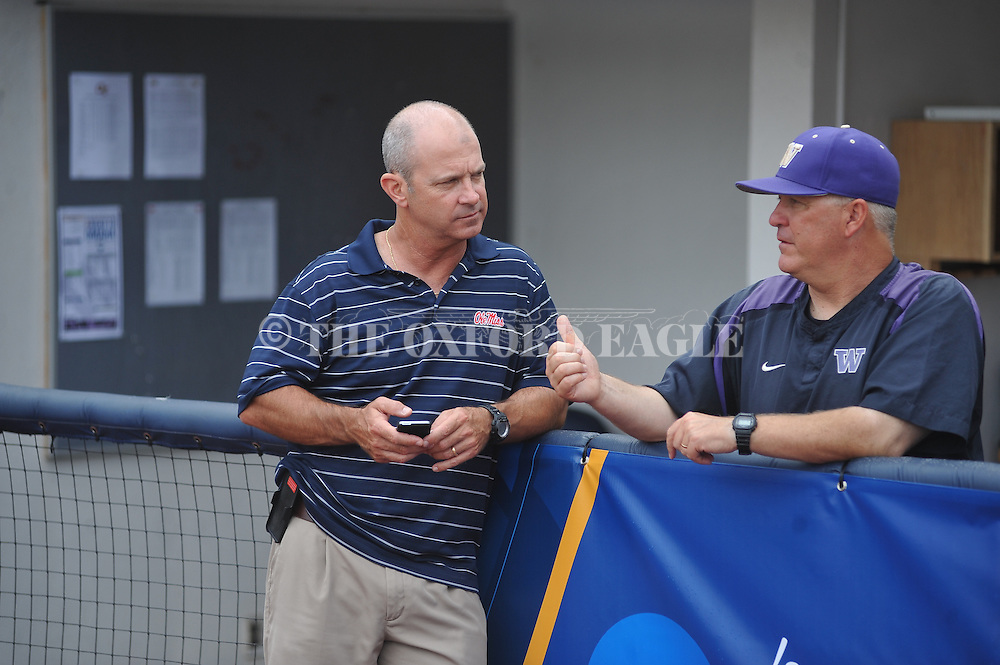 Mississippi head coach Mike Bianco (left) visits with Washington head coach Lindsay Meggs during a rain delay at Georgia Tech vs. Washington at the NCAA Oxford Regional at Oxford-University Stadium on Friday, May 30, 2014. The game was eventually postponed until Saturday. (AP Photo/Oxford Eagle, Bruce Newman)