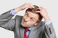 Close-up of confused businessman touching head with funny face over colored background