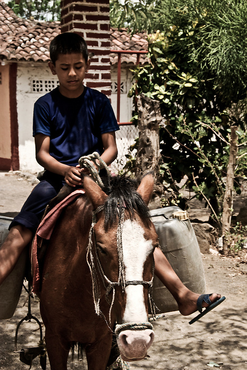 A boy leaves his home in Ometepe Island on his Caballito, a smaller, heartier version of a horse. Despite their famished and often times sickly appearance these animals are strong and a major resource to the people of Nicaragua.
