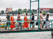 09 OCTOBER 2012 - BANGKOK, THAILAND:  Buddhist monks walk along a pier to a waiting ferry on Chao Phraya River. They were returning to their temple on the Thonburi side of the river.     PHOTO BY JACK KURTZ