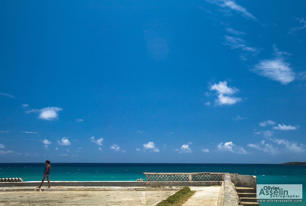 A girl walks down the seafront in Baracoa, Cuba on Friday July 11, 2008.
