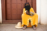 MARRAKECH, MOROCCO - May 27 2018 -Portrait of a lady selling bracelets sitting infront of Mosque doorway outside the Saadian tombs in the Marrakech, Medina, Morocco