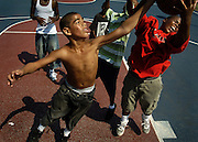BALTIMORE, MD--8/25/2006--Nick Leonard, 14, left, and Dashawn Jones, 13, far right, spar over the ball after a rebound while playing basketball with friends at Druid Hill Park Friday, August 25, 2006..GLENN FAWCETT