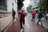 Un manifestant court afin de se protéger des gaz lacrymogènes des forces de police, à proximité de l'ambassade de France. // Des affrontements entre la police et les manifestants ont éclaté dans le centre de Tunis, notamment avenue Habib Bourguiba, faisant (selon Associated Press) 3 morts (prétendument par balle) et 12 blessés parmi les manifestants, Tunis le 26 février 2011.