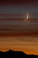 A crescent moon glows in the warm colors of sunset as it sets behind the crest of the Sierra.