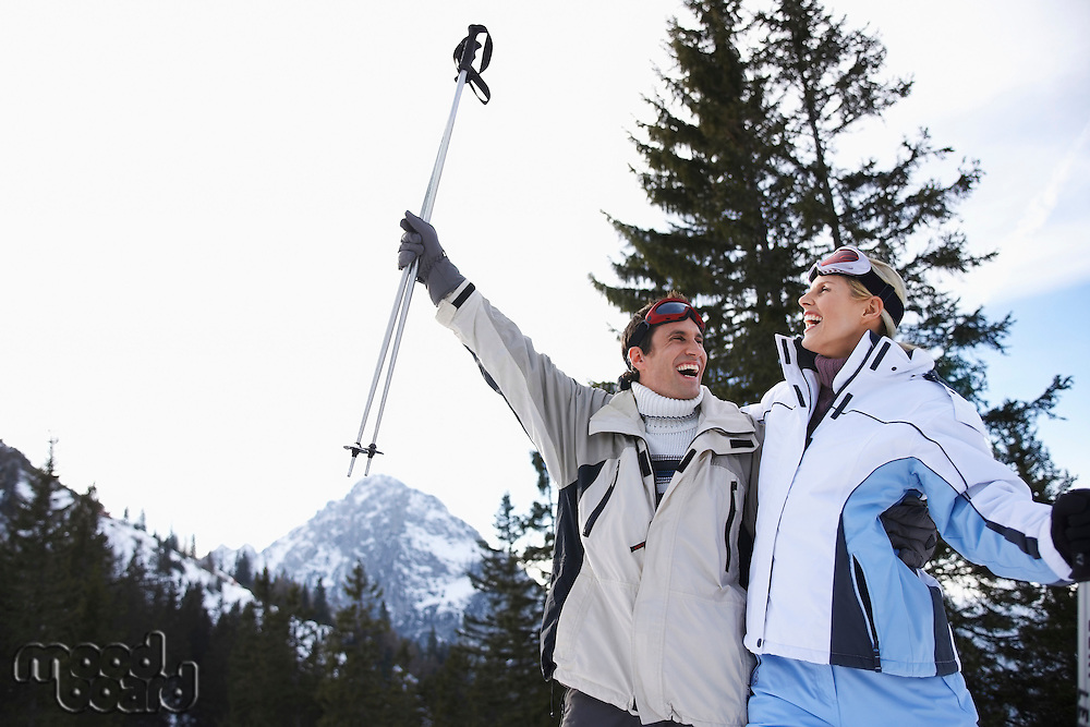 Couple laughing standing on ski slope low angle view