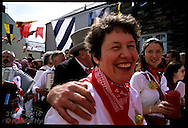 Woman smiles as grand marshall grabs her shoulder in parade of the red Obby Oss at Padstow's May Day fest; Cornwall, England.