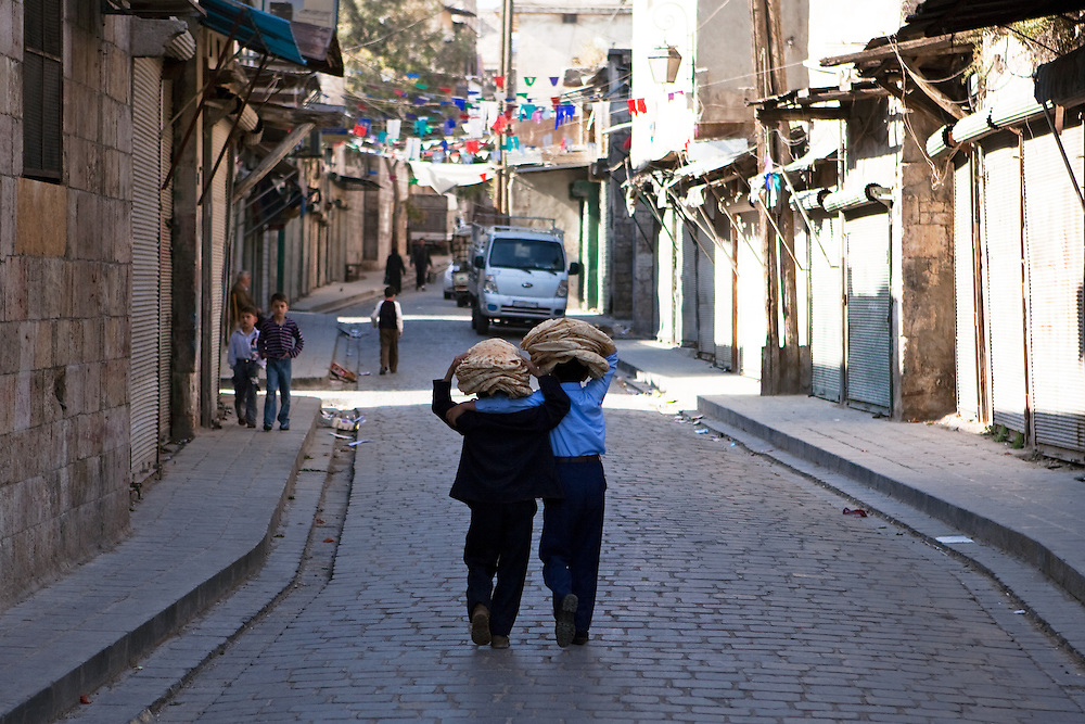 Two young boys walk home, with fresh flatbread, a daily staple, balanced on their heads, Aleppo, Syria