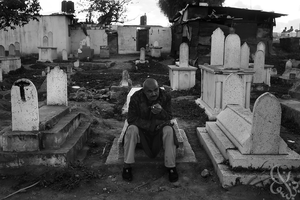 A Palestinian man pauses to smoke a cigarette between the graves January 18, 2009 during funerals for the Samouni family at the al Bahriyah cemetery in Gaza City. All 28 members of the family were killed by an apparent airstrike on their home during the 21 day Israeli operation in Gaza and finally dug out of the rubble today by extended family members following a ceasefire announcement by the Israelis last night.