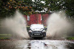 © Licensed to London News Pictures. 07/10/2015. Leeds, UK. Picture shows a vehicle driving through the water left on the road after a heavy rainfall at Temple Newsam park in Leeds. Photo credit: Andrew McCaren/LNP