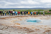 A crowd watches as Strokkur geyser erupts. Right before it erupts, there is something like a large bubble of water first. Haukadalur, Iceland.