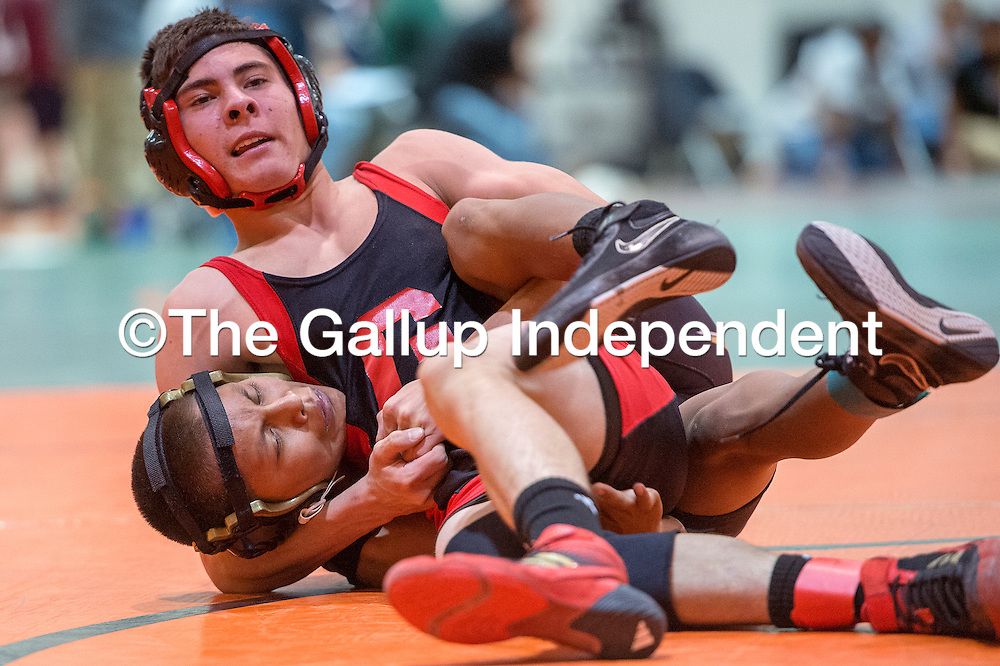 121813       Cable Hoover<br /> <br /> Grants Pirate Ed Woodbury rolls over Chinle Wildcat Raul yazzie Thursday at Wingate High School.