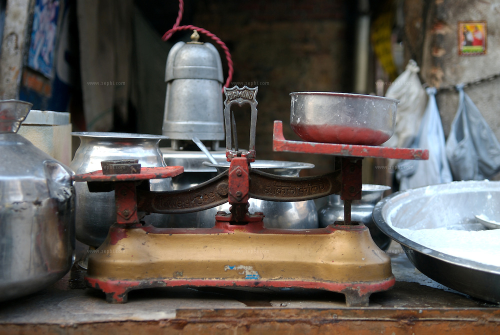 An old scale used to weigh Dahi (yogurt) at a stall in Delhi. The towering metal object in the back is a mixer-blender for making Lasi, a yogurt drink.