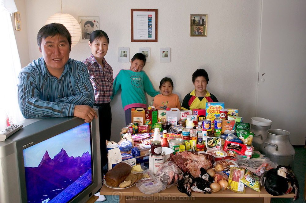 (MODEL RELEASED IMAGE). The Madsen family in their living room in Cap Hope village, Greenland, with a week's worth of food. Standing by the TV are Emil Madsen, 40, and Erika Madsen, 26, with their children (left to right) Martin, 9, Belissa, 6, and Abraham, 12. The Madsen family is one of the thirty families featured in the book Hungry Planet: What the World Eats (p. 144).