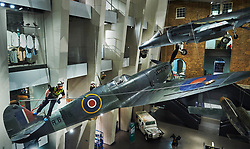 © Licensed to London News Pictures. 01.02.18 London, UK.  A specialist team from Arco Total Access are suspended by ropes to dust a Supermarine Spitfire Mark1A at the Imperial War Museum, London. The rare aircraft is one of few remaining in it's original 1940's paint and is given a clean-up every three years.<br />