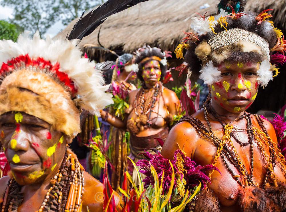 Women of the Selehoto Alunumuno tribe standing in a group. Her face is painted and she is wearing traditional dress made from animal fur, flowers, feathers, beads and leaves. Photo taken by a small village in the Papua New Guinea highlands.