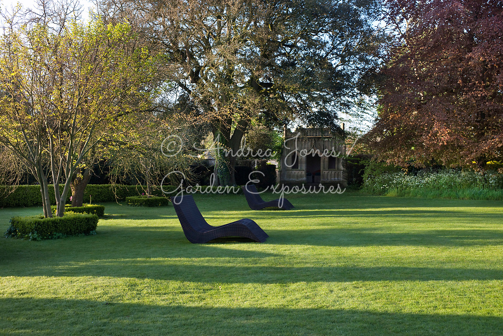 Wicker reclining chairs on the Croquet Lawn in front of The Gothic Summerhouse at Barnsley House