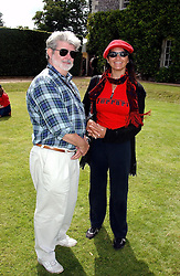 """Film director GEORGE LUCAS and ALEJA at a luncheon hosted by Cartier at the 2004 Goodwood Festival of Speed on 27th June 2004.  Cartier sponsored the """"Style Et Luxe' for vintage cars on the final day of this annual event at Goodwood House, West Sussex."""