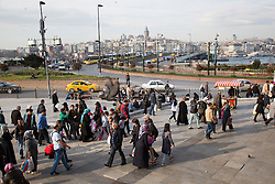 People pass in the Eminonu area, near the Spice Bazaar and New Mosque. In the background the Galata Bridge is seen.