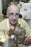 Portrait of a skilled mature man repairing watch in workshop